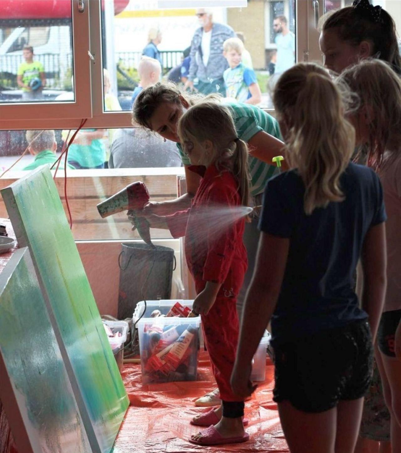Jongeren geven een graffiti-workshop aan kinderen.